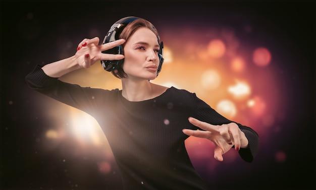 Wizerunek dziewczyny w czarnej sukience ze słuchawkami w nocnym klubie. koncepcja strony. różne środki przekazu
