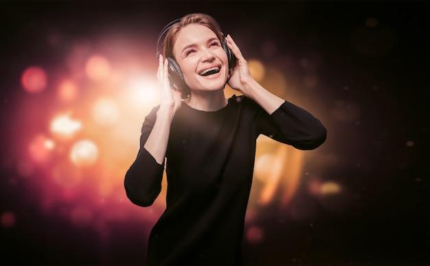 Wizerunek Dziewczyny W Czarnej Sukience Ze Słuchawkami W Nocnym Klubie. Koncepcja Strony. Różne środki Przekazu Premium Zdjęcia