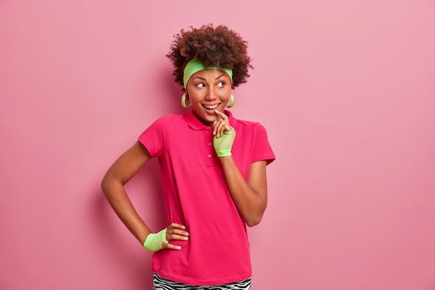 Wizerunek dziewczyny z kręconymi włosami ma przebiegły, wesoły wyraz twarzy, wygląda z zamiarem realizacji planu, ubrana w luźne ciuchy