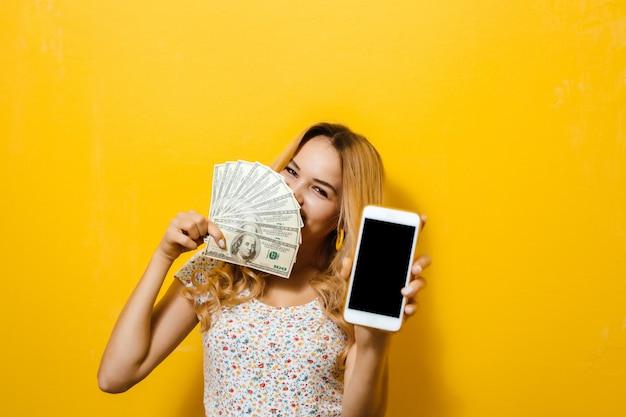 Wizerunek emocjonalnej młodej blond dziewczyny mienia banknoty i czarny parawanowy telefon komórkowy na żółtej ścianie