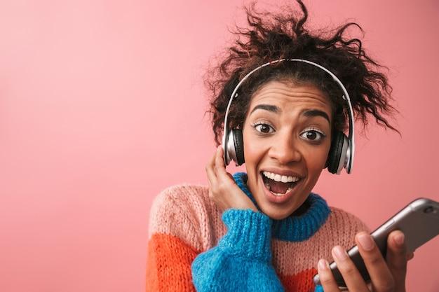 Wizerunek emocjonalnej pięknej młodej kobiety afryki pozowanie na białym tle słuchanie muzyki w słuchawkach za pomocą telefonu komórkowego.