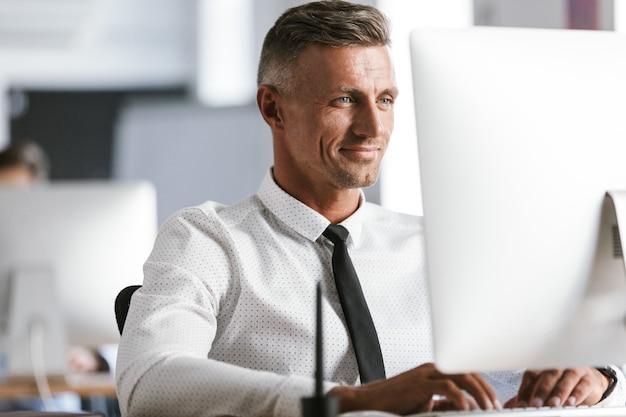 Wizerunek europejski rzeczowy mężczyzna 30-tych ubrany w białą koszulę i krawat, siedzący przy biurku w biurze i pracujący przy komputerze
