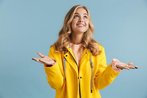 Wizerunek europejskiej kobiety lat 20. ubrana w żółty płaszcz przeciwdeszczowy, patrząc w górę