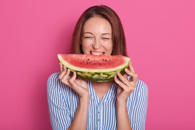 Wizerunek gryźć dużego plasterek słodki arbuz młoda kobieta