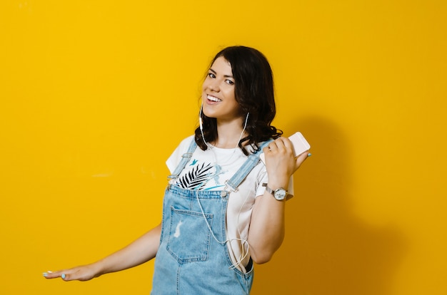 Wizerunek jest ubranym słuchawki śpiewać szczęśliwa kobieta odizolowywa nad kolor żółty ścianą