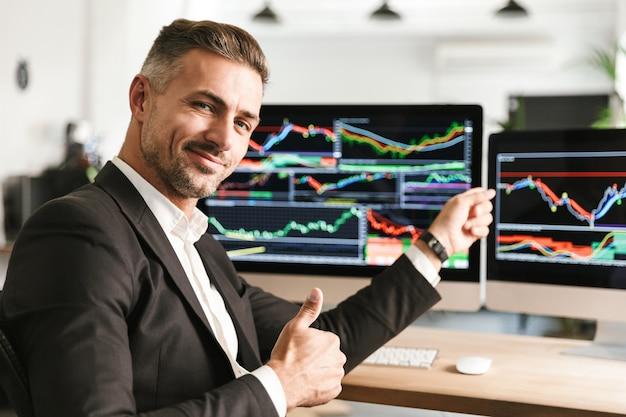 Wizerunek kaukaski biznesmen 30s ubrany w garnitur pracujący w biurze na komputerze z grafiką i wykresami na ekranie
