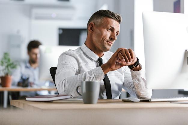 Wizerunek kaukaski biznesmen lat 30. ubrany w białą koszulę i krawat, siedzący przy biurku w biurze przy komputerze i patrząc na zegarek