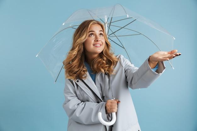 Wizerunek kaukaski kobieta lat dwudziestych ubrana w płaszcz przeciwdeszczowy stojąca pod przezroczystym parasolem