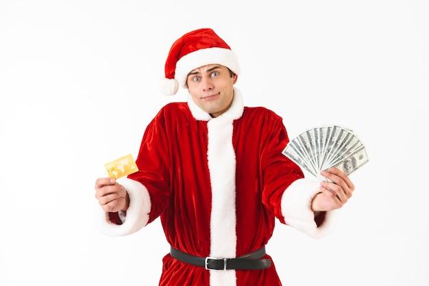 Wizerunek kaukaski mężczyzna 30s w stroju świętego mikołaja trzymającego dolary i kartę kredytową