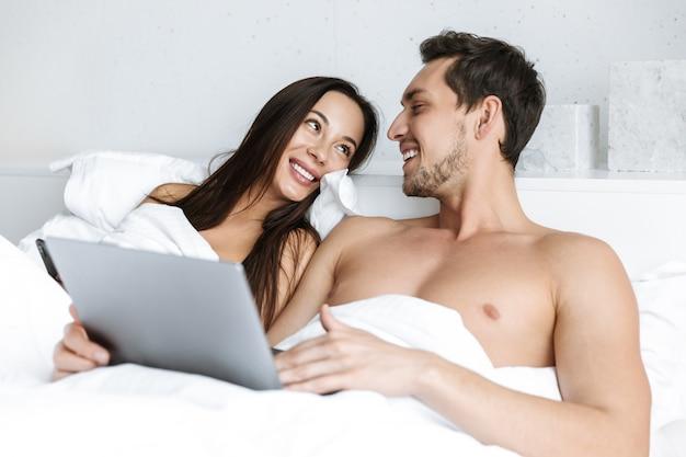 Wizerunek kaukaski para za pomocą laptopa i smartfona, leżąc w łóżku w domu lub apartamencie hotelowym