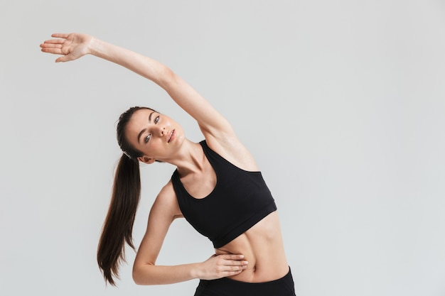 Wizerunek kobiety fitness piękny młody sport zrobić ćwiczenia na białym tle nad szarą ścianą.