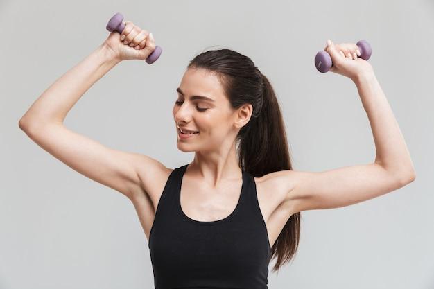 Wizerunek kobiety fitness piękny młody sport zrobić ćwiczenia z hantlami na białym tle nad szarą ścianą.