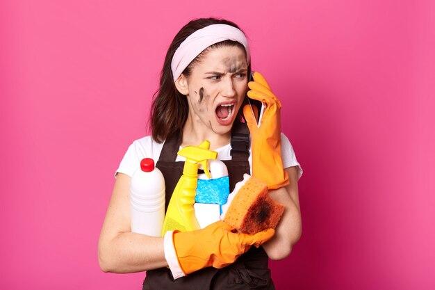 Wizerunek krzycząca kobieta mówi na telefonie komórkowym podczas gdy czyścić w domu, ubiera t koszula, fartuch i hairband, brunetki damy mienia gąbka i detergenty, wzorcowy pozować odizolowywam nad menchii ścianą.