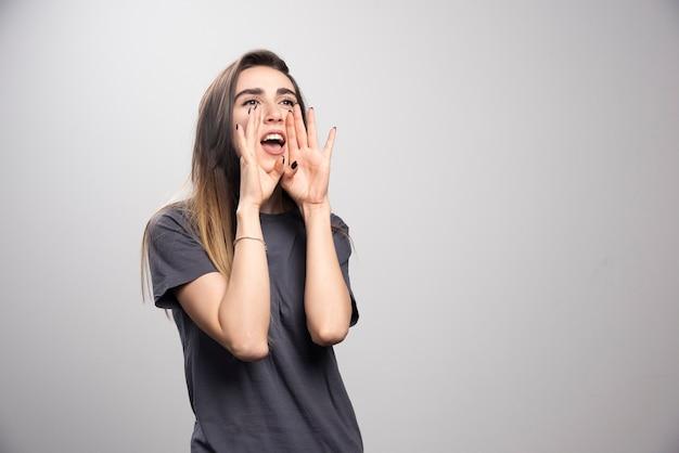 Wizerunek krzyczeć młoda ładna kobieta pozowanie na białym tle na tle szarej ścianie.