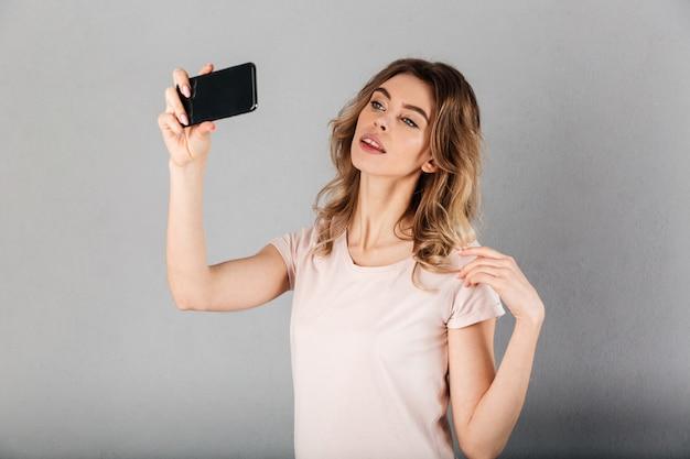 Wizerunek ładna kobieta w koszulce robi selfie na smartphone nad popielatym