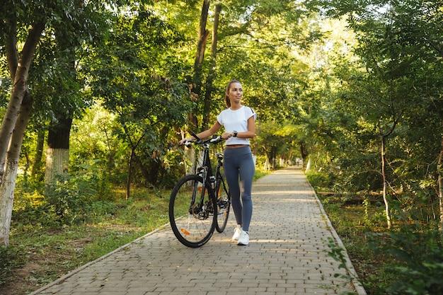 Wizerunek ładnej kobiety 20s spaceru z rowerem przez zielony park, w słoneczny dzień