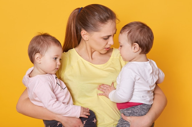 Wizerunek matki z jej słodkimi dziećmi, pozuje w studiu. bliźniaczki mumia i dziewczęta, ubrane od niechcenia, mama opowiada swoim córkom o dniu matki. małe dzieci słuchają opowieści o mamusiach i obejmują ją.