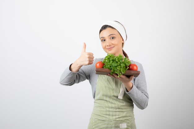 Wizerunek miłej kobiety z drewnianą deską pietruszki i pomidorów pokazującą kciuk w górę