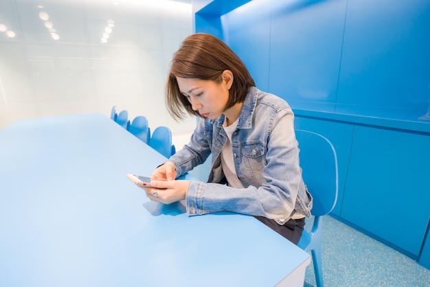 Wizerunek młoda dama używa smartphone przy współpracowaniem