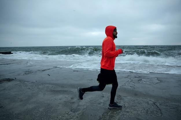 Wizerunek młodego aktywnego brodatego mężczyzny wykonującego poranne ćwiczenia nad morzem, biegnącego wzdłuż wybrzeża w zimną, ponurą pogodę, ubrany w ciepłe, sportowe ubrania. męski model fitness