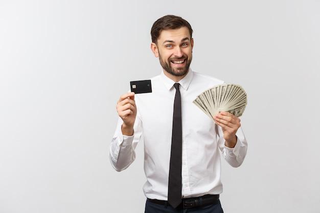 Wizerunek młodego biznesmena pozowanie na białym tle nad białą ścianą posiadania karty kredytowej i pieniędzy