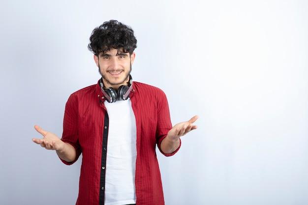 Wizerunek młodego faceta w słuchawkach stojących na białym tle. wysokiej jakości zdjęcie