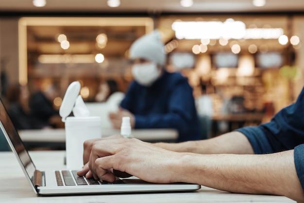 Wizerunek młodego mężczyzny pracującego na laptopie w miejscu publicznym