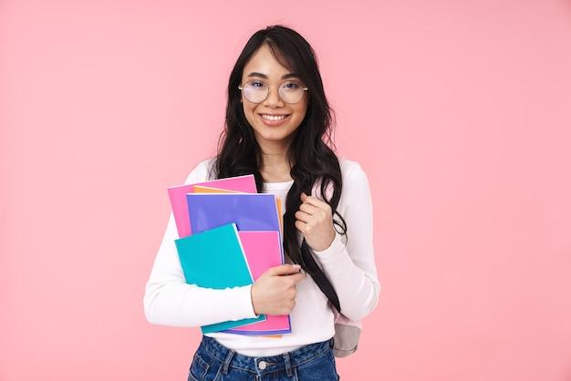 Wizerunek młodej brunetki azjatyckiej studentki w okularach trzymającej papierowe foldery odizolowane na różowo