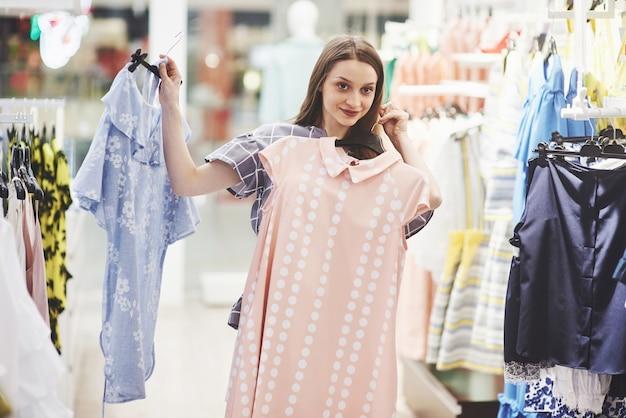 Wizerunek młodej damy pozycja w odzieżowym sklepie indoors wybiera suknie. patrząc na bok