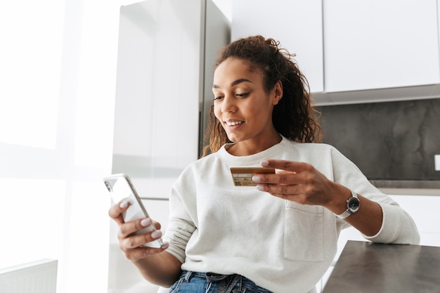 Wizerunek młodej dziewczyny afroamerykanów przy użyciu telefonu komórkowego i karty kredytowej, siedząc przy stole w jasnym salonie