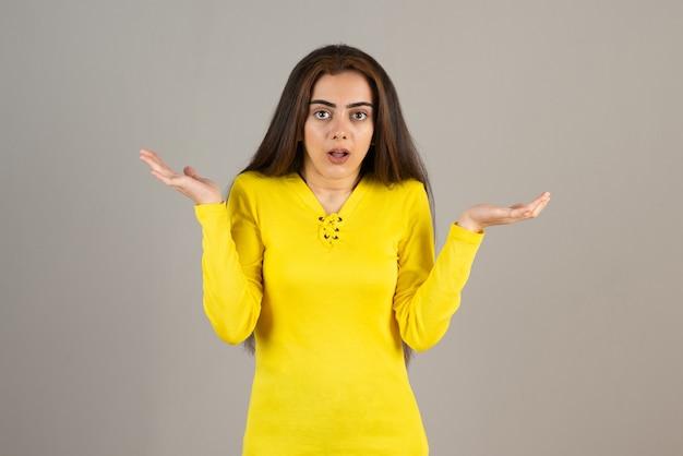 Wizerunek młodej dziewczyny w żółtej górze stojącej i pozowanie na szarej ścianie.