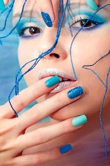 Wizerunek młodej dziewczyny z niebieskim makijażem i manicure z piaskowym błyszczącym kolorowym wzorem paznokci z błyszczącymi ornamentami na głowie.
