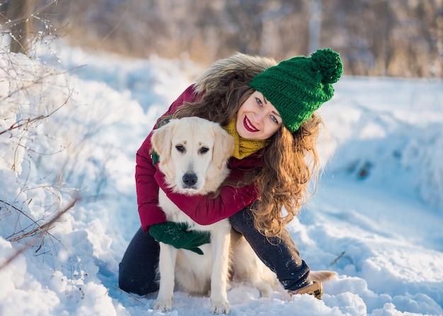 Wizerunek młodej dziewczyny z psem przytulanie biały golden retriever, na zewnątrz w okresie zimowym