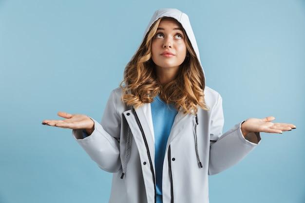Wizerunek młodej kobiety 20s ubrana w płaszcz przeciwdeszczowy z kapturem patrząc w górę
