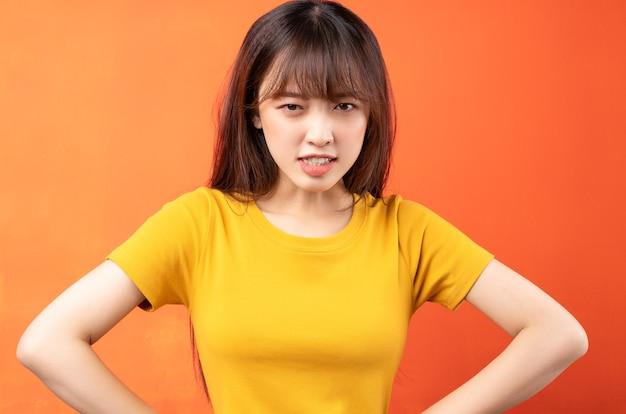 Wizerunek młodej kobiety azji na sobie żółtą koszulkę na pomarańczowo
