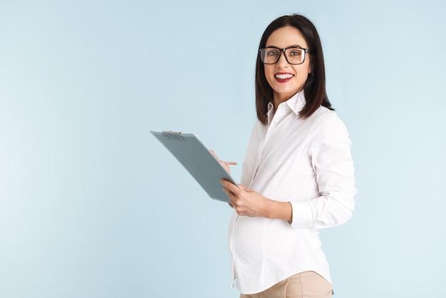 Wizerunek młodej kobiety biznesu w ciąży na białym tle gospodarstwa schowka.