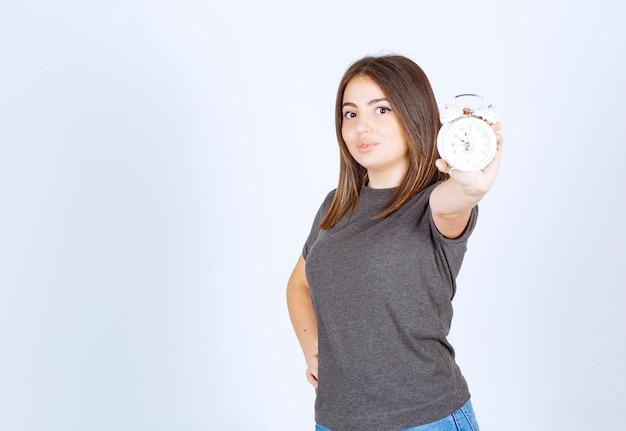 Wizerunek młodej kobiety ładnej modelu pokazujący budzik.
