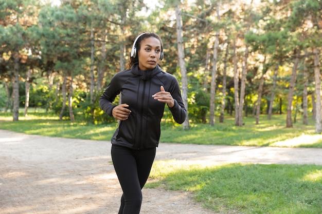 Wizerunek młodej kobiety lat 20. ubrana w czarny dres i słuchawki, ćwicząca podczas biegania przez zielony park