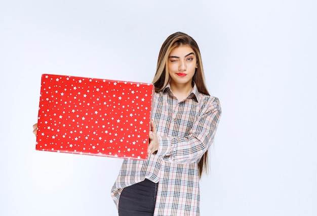 Wizerunek młodej kobiety model stojący i trzymający czerwone pudełko.