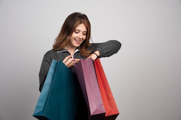 Wizerunek młodej kobiety patrzącej na torby sklepowe.