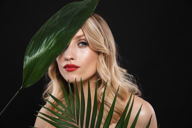 Wizerunek młodej kobiety piękne z jasny makijaż czerwone usta pozowanie na białym tle z liści zielony kwiat.