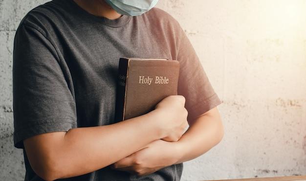 Wizerunek młodej kobiety trzymającej biblię mocno przy piersi. chrześcijaństwo gotowe do okazania miłości boga