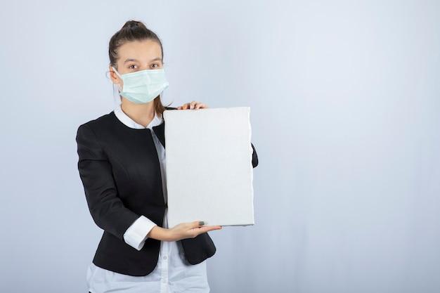Wizerunek młodej kobiety w masce na twarzy, trzymając puste płótno na białej ścianie. wysokiej jakości zdjęcie