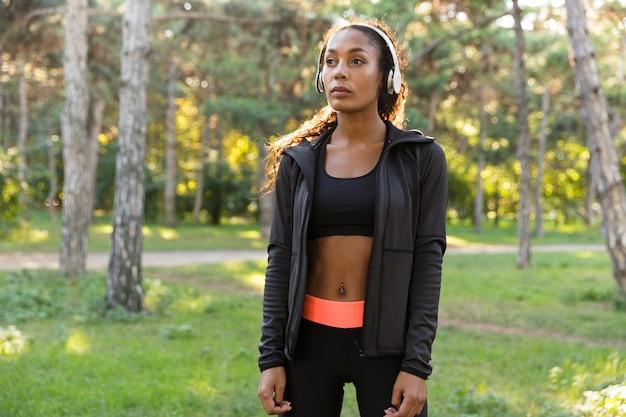Wizerunek młodej kobiety w wieku 20 lat ubrana w czarny dres i słuchawki, spacerująca po zielonym parku