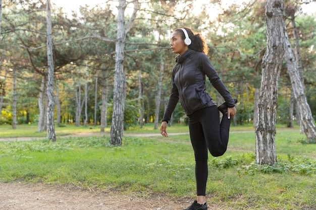 Wizerunek młodej kobiety w wieku 20 lat ubrana w czarny dres uprawiający sport i rozciągająca się w zielonym parku