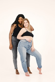 Wizerunek młodej kobiety. wielorasowe przyjaciele pozowanie na białym tle na tle białej ściany.