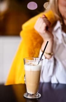 Wizerunek młodej kobiety z lampką latte, siedząc w kawiarni.
