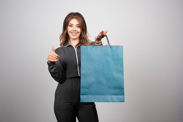 Wizerunek młodej kobiety z torbą sklepową pokazującą kciuk w górę.