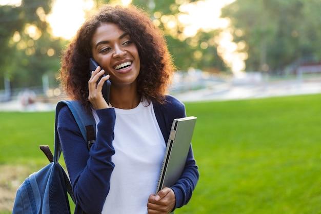 Wizerunek młodej pięknej afrykańskiej studentki spaceru w parku trzymając laptopa rozmawia przez telefon komórkowy.