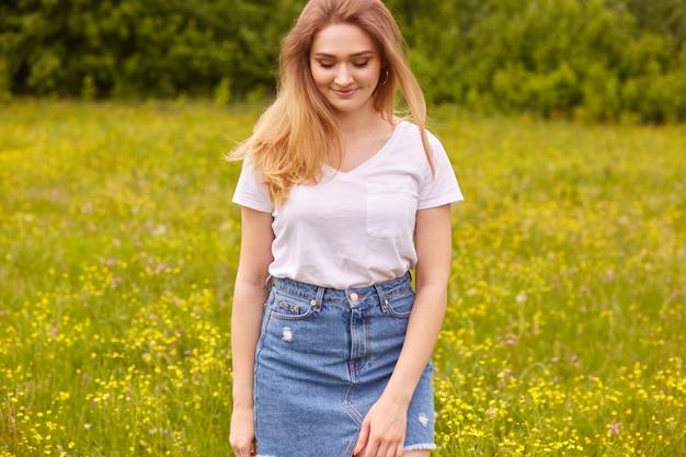 Wizerunek młodej pięknej kaukaskiej dziewczyny w białej koszulce i niebieskiej dżinsowej spódnicy, pozującej na łące i spoglądającej w dół, ma długie proste blond włosy, wyraża radość i szczęście.